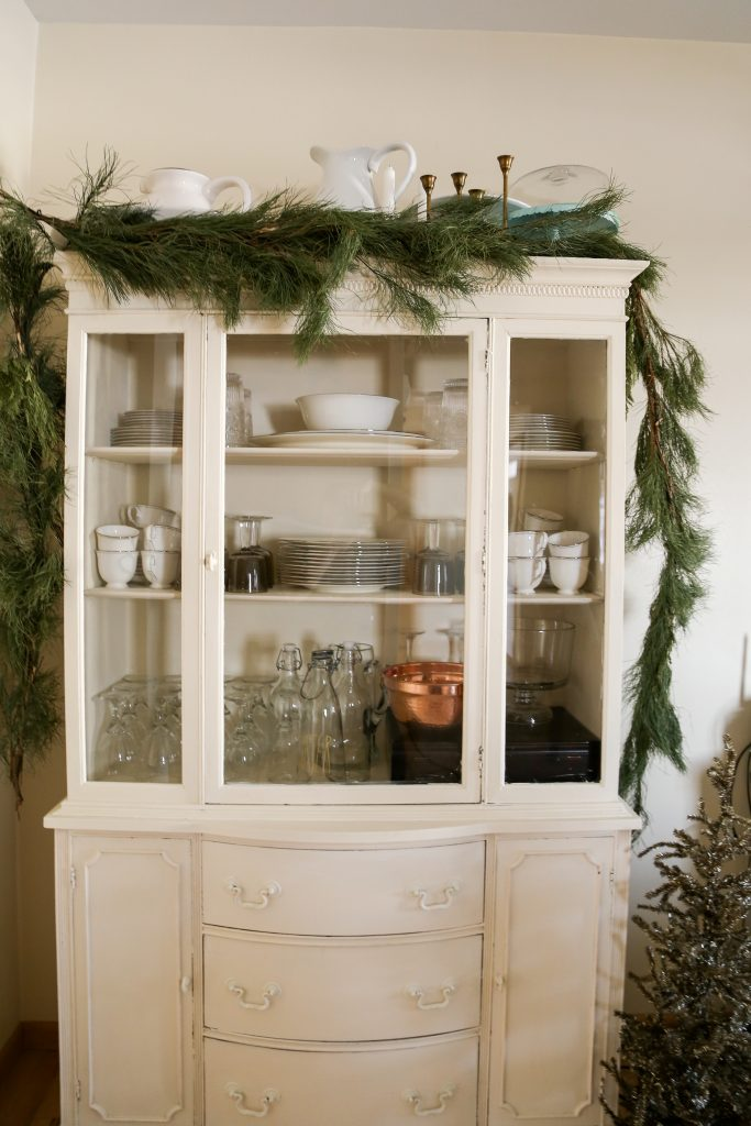 Simple green garland on the china hutch, and a gold christmas tree decorate the farmhouse for Christmas.