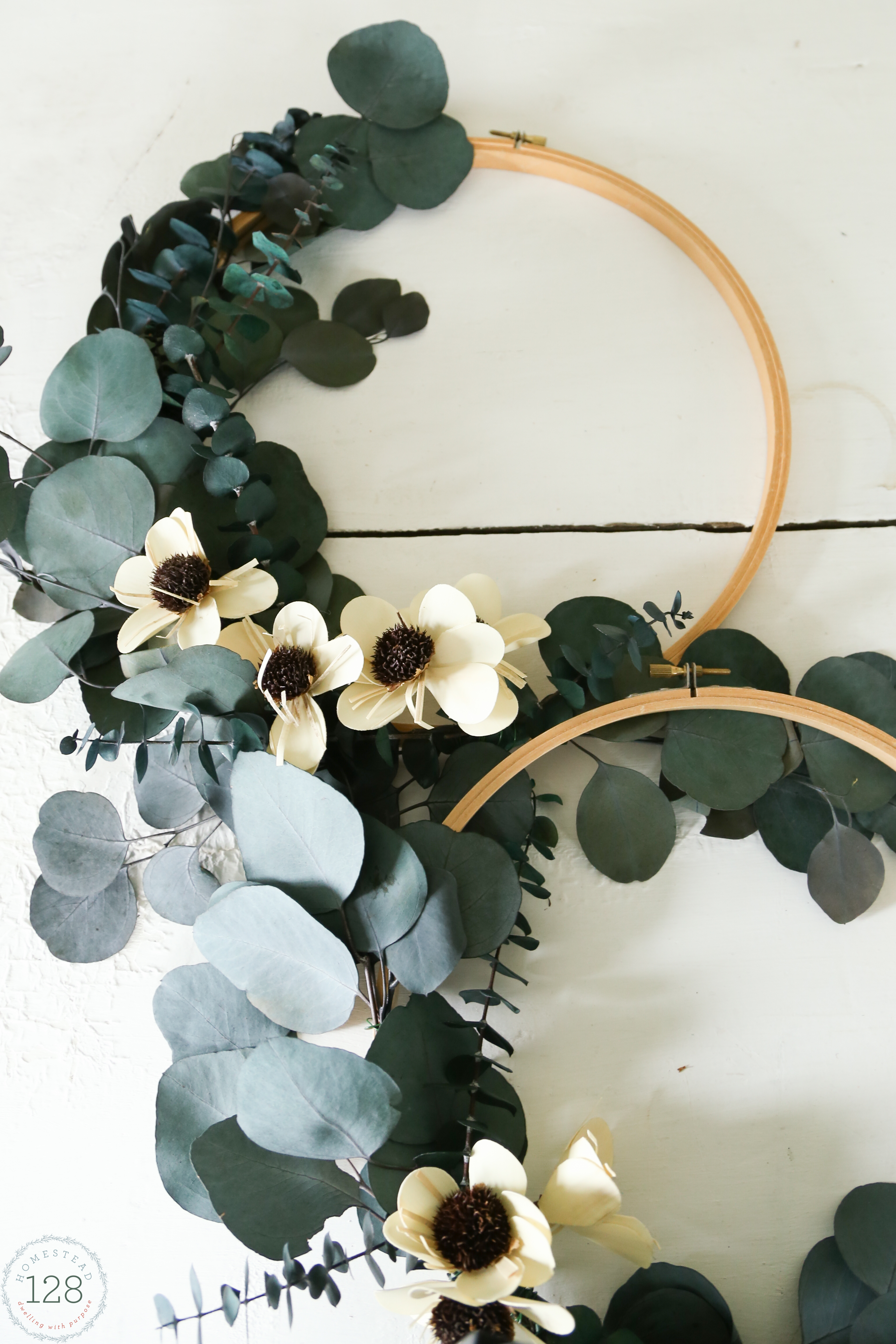 Create a wreath for the season with an embroidery hoop and dried natural stems.