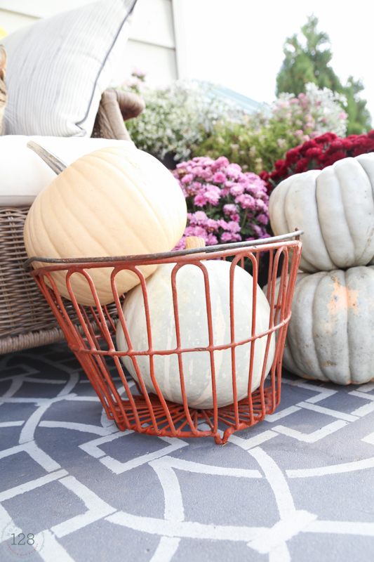 The red egg basket for storing pumpkins on the fall farmhouse front porch.