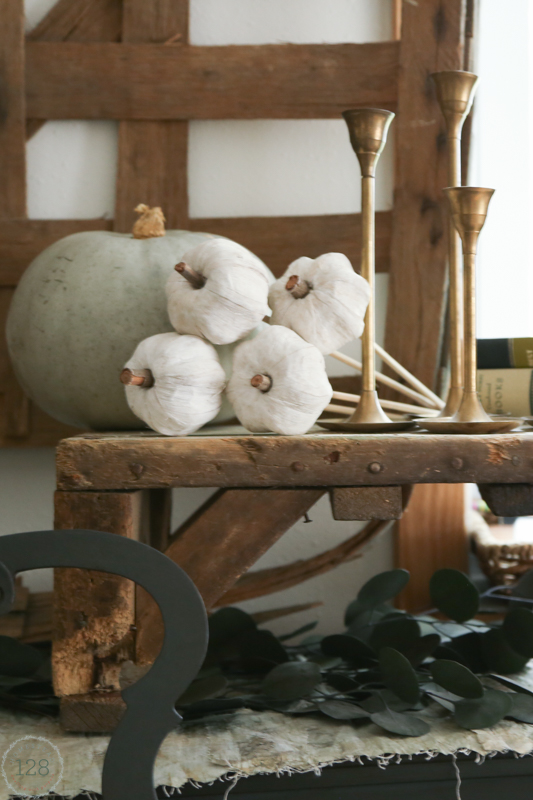 Rustic wood shelf with white and light green pumpkins for decorating the fall farmhouse.