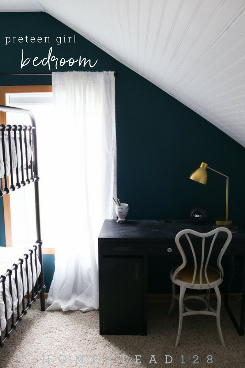 Preteen girl bedroom with dark moody walls and light white beadboard.