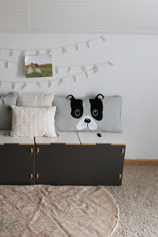 Toy storage boxes used as a reading bench with added pillows and string lights for hanging pictures.