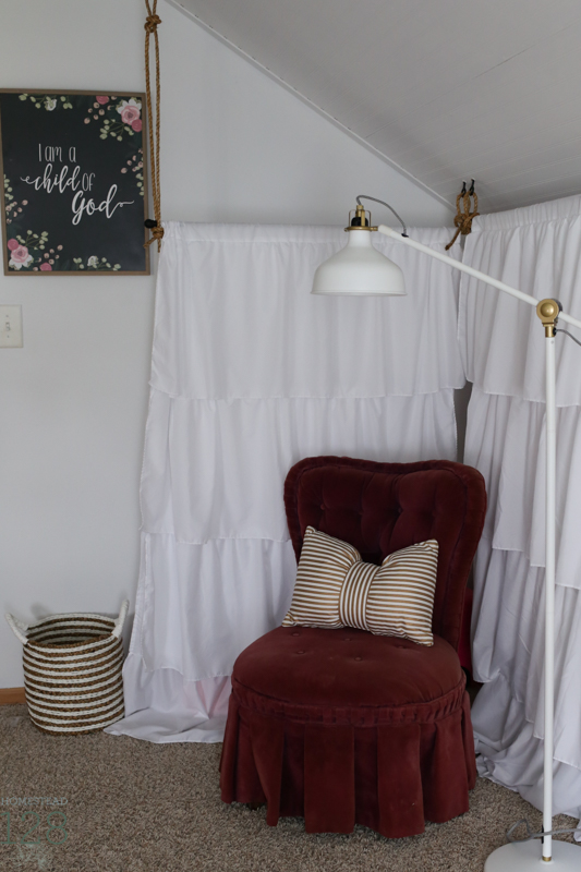Curtains for hiding toy storage, and a small velvet chair create a reading nook.