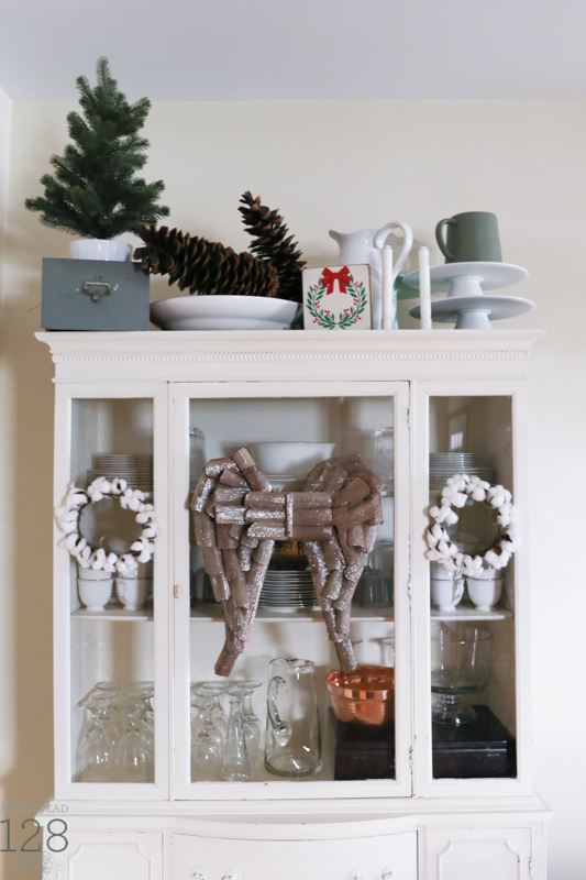 Extra large pinecones with a touch of green, cotton and wooden angel wings decorate the china cabinet at Christmas.