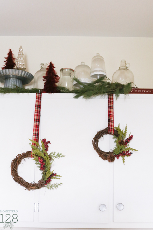 Asymmetrical wreaths hang from storage cupboards in the Christmas farmhouse.