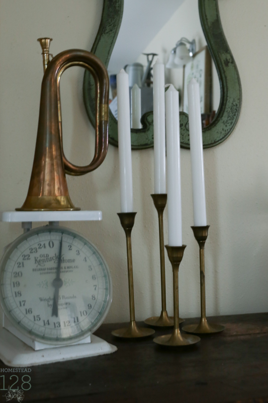 Touches of brass for Christmas with old brass candlesticks and horn along with a white scale.