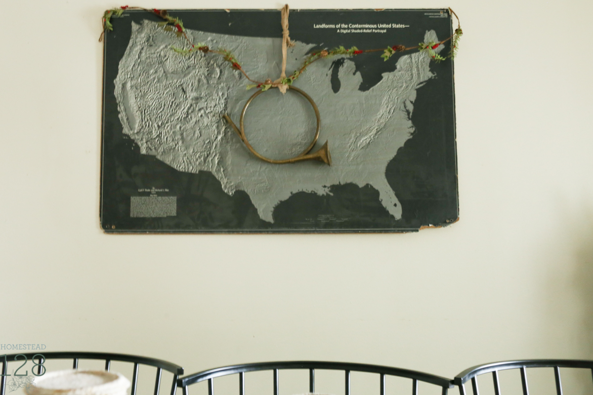 Vintage and torn black and white school map is decorated with some simple garland and a brass horn for Christmas.
