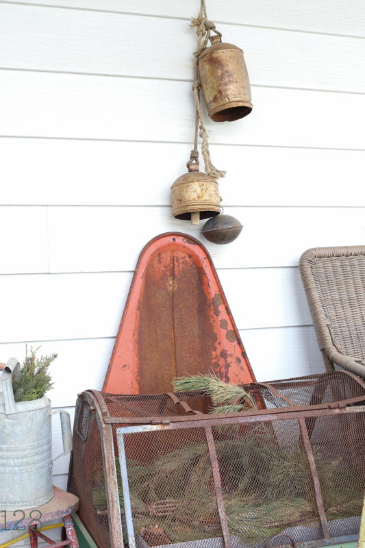 Farmhouse Christmas front porch decorating. Old red sled and brass bells with the pine branch filled greenhouse and watering can.