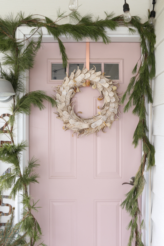 Farmhouse Christmas front porch decorating. A pink door is decorated with loads of garland and pine branches, a vintage door, and galvanized tin.