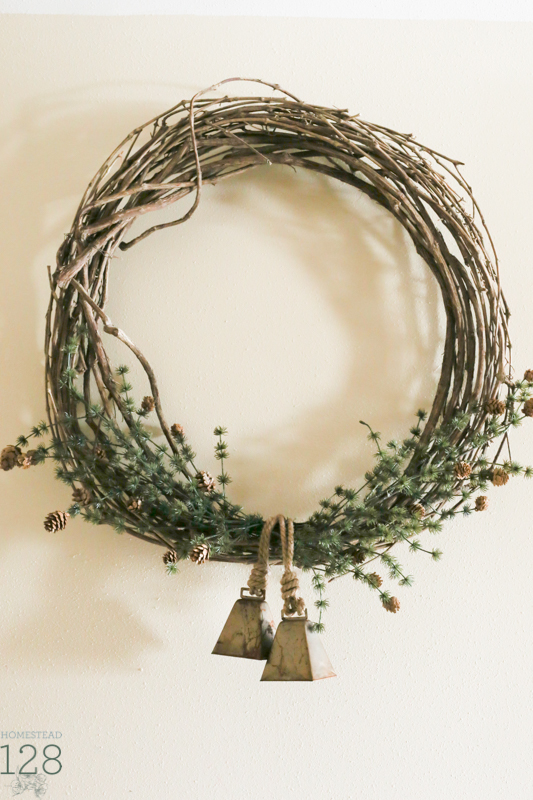 Simple Christmas wreath. Farmhouse Christmas decorating. Extra large wreath hung in the hallway with faux pine branches and brass bells.