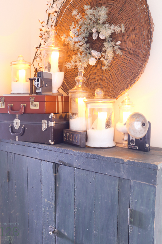 Farmhouse Christmas decorating. Old cupboard is decorated with small suitcases, and glass jars filled with candles, faux snow, and snow globe decor.