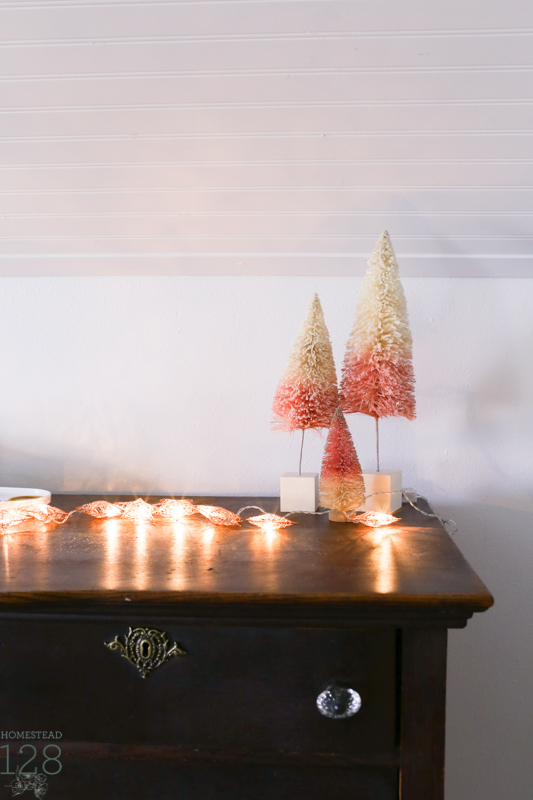 Farmhouse Christmas decorating. Girls bedroom decorated for Christmas with pink bottle brush trees and rose gold lights.