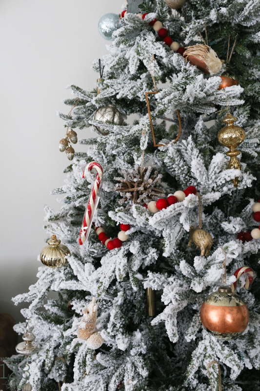 Farmhouse Christmas. A flocked Christmas tree is decorated with copper, gold and red.