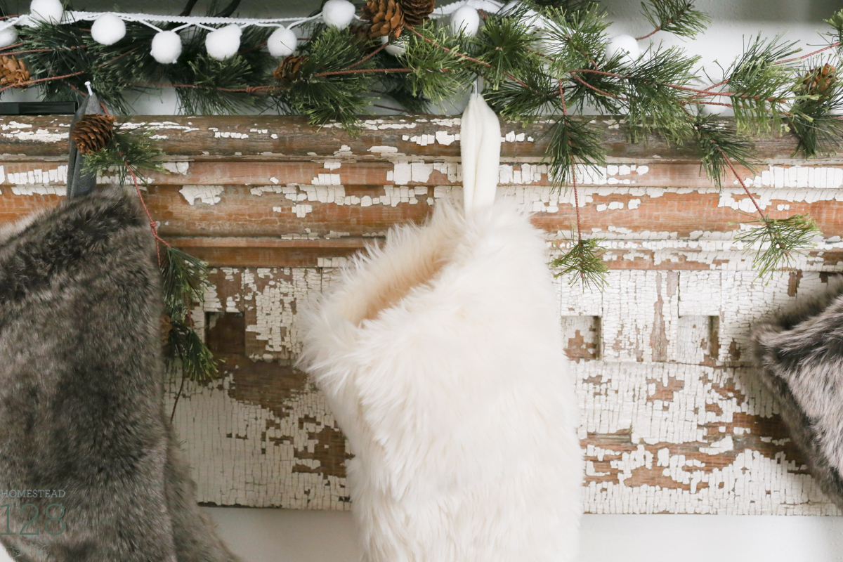Farmhouse Christmas decorating. Furry and neutral stockings hung on a chippy white mantle with pine tree garland.
