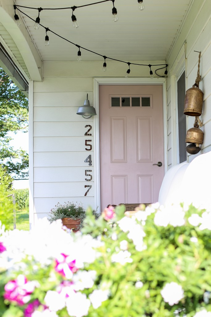 Farmhouse front porch with light pink front door and string lights.