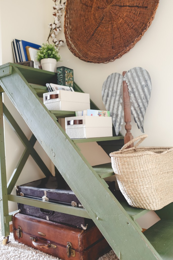 Memory storage suitcases tucked under storage ladder.