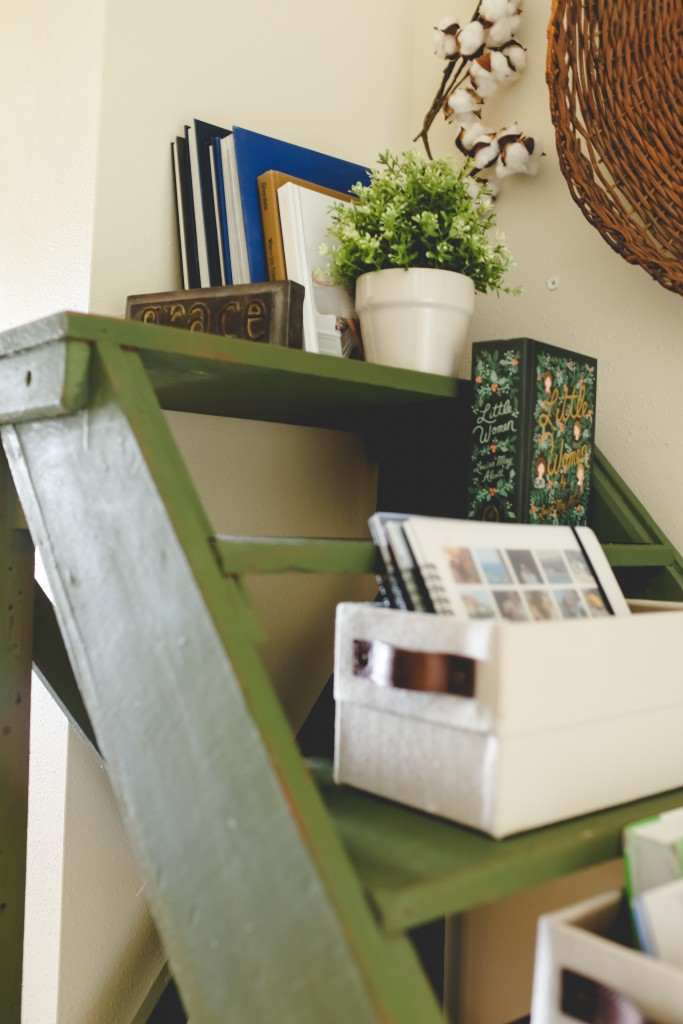 Vintage ladder turned into book storage with baskets and book ends.