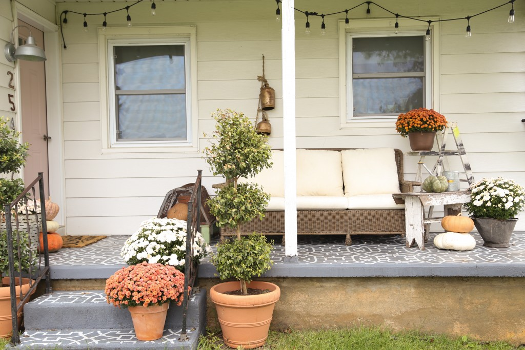 Farmhouse front porch ready for fall with oranges and whites.