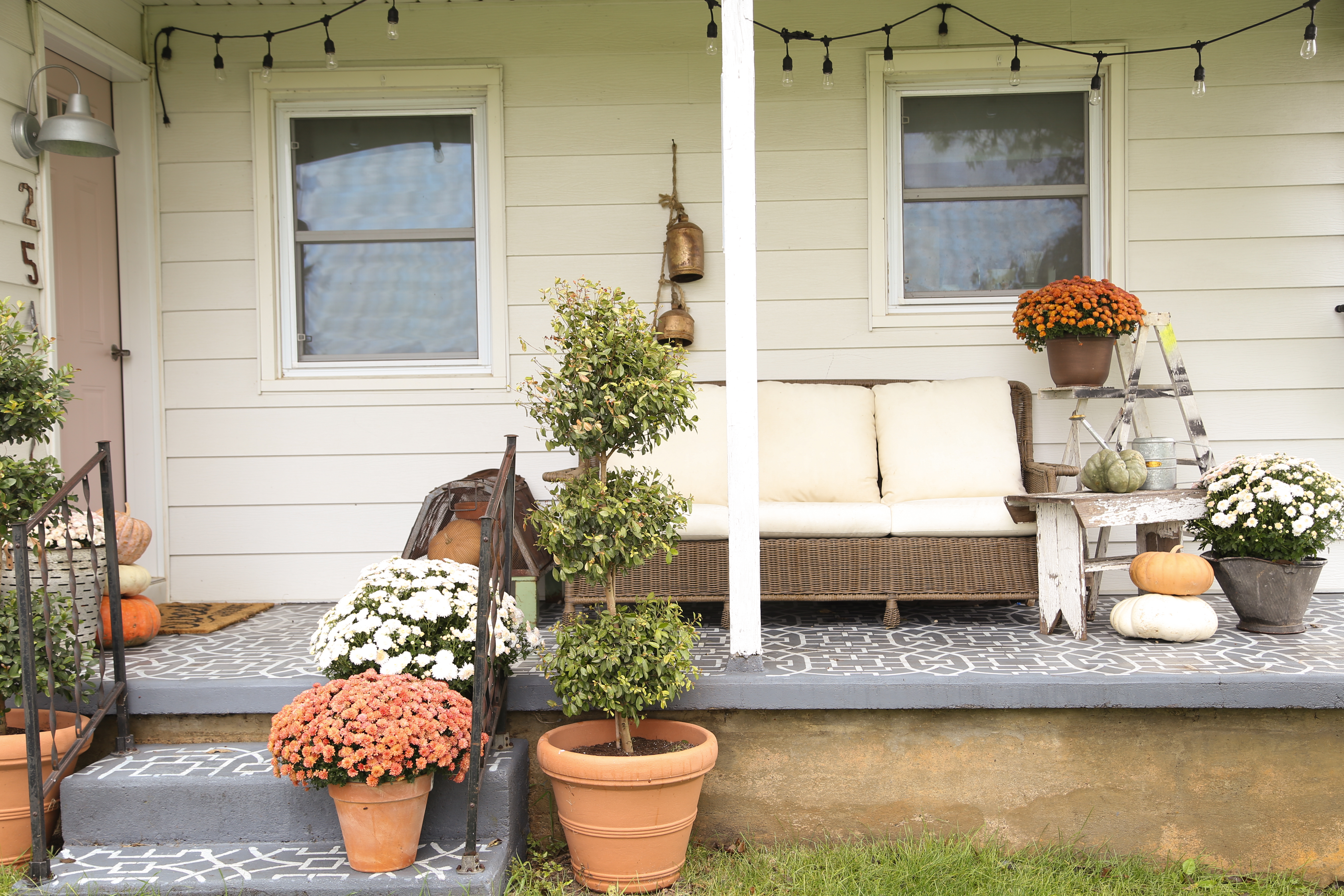 Farmhouse front porch ready for fall with oranges and whites