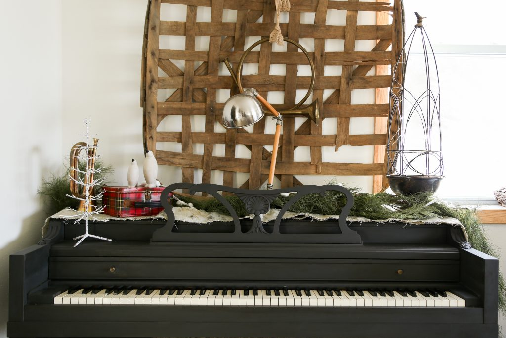 The black piano is decorated for Christmas with a tobacco basket, garland and touches of white.