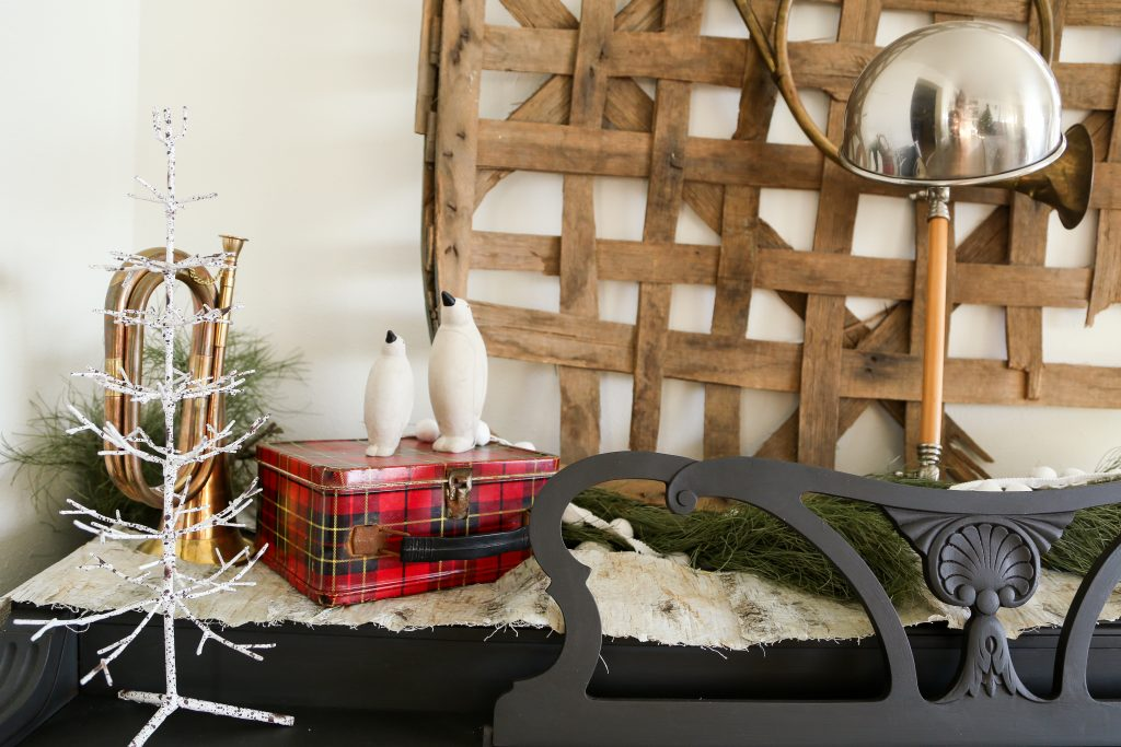 A brass trumpet, plaid, and a large tobacco basket decorate the black piano for Christmas.