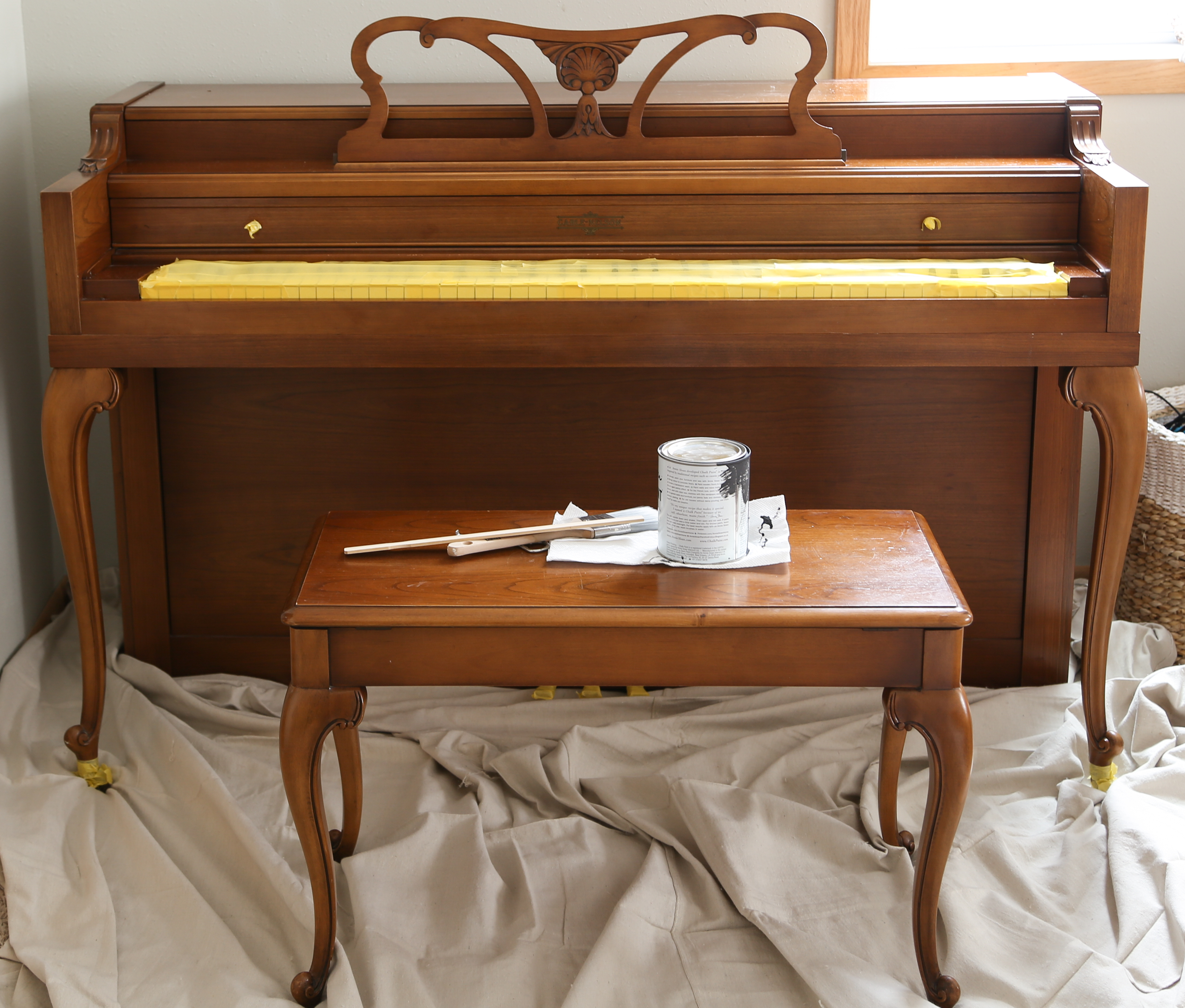Prepping the piano for painting with painters tape.