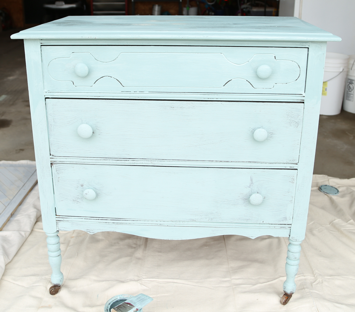 A dresser is lightly painted before gradual sanding is applied to resemble a balayage effect.