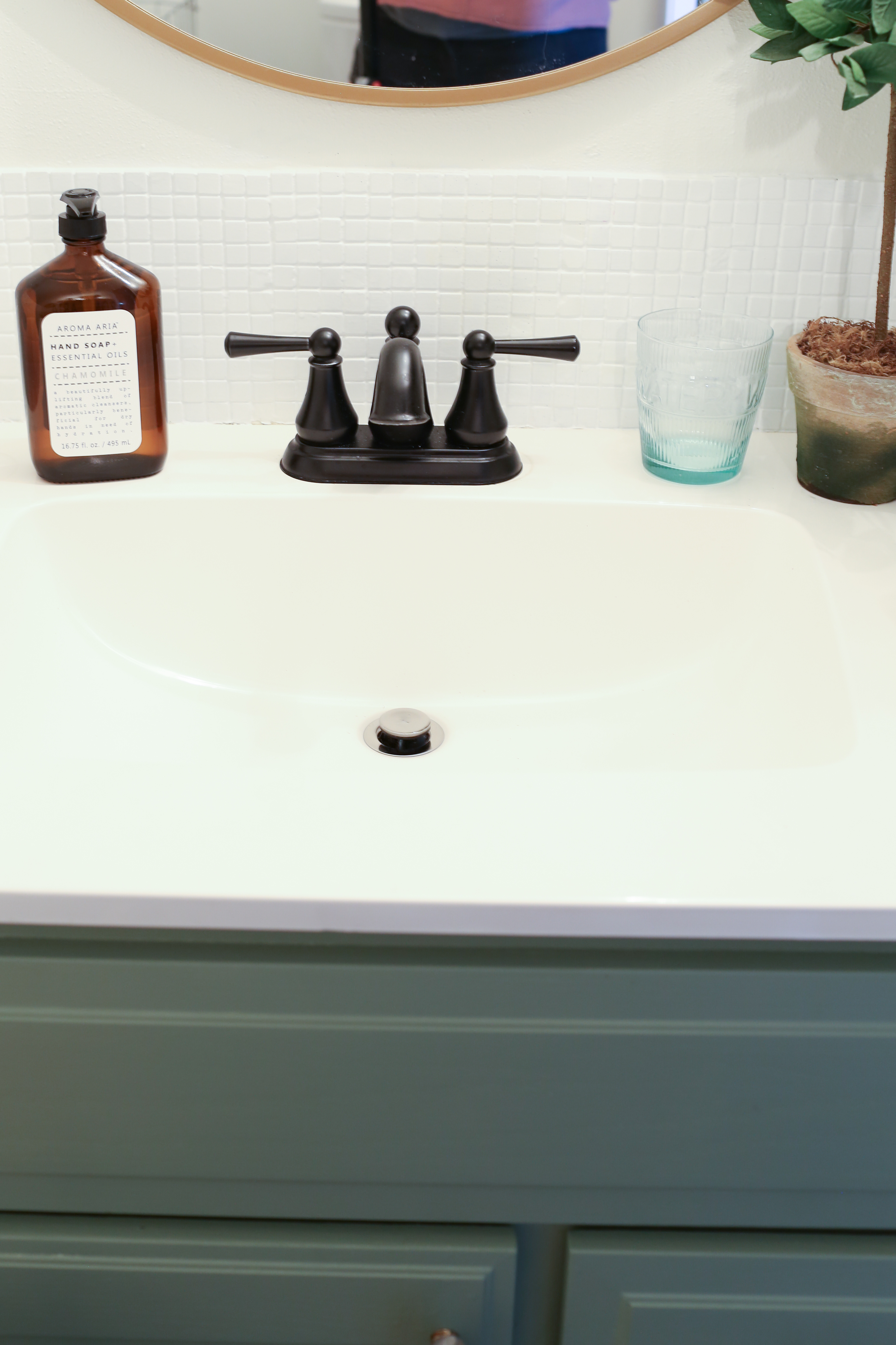 The glass tile backsplash is painted a matte white to give the bathroom a clean farmhouse feel.