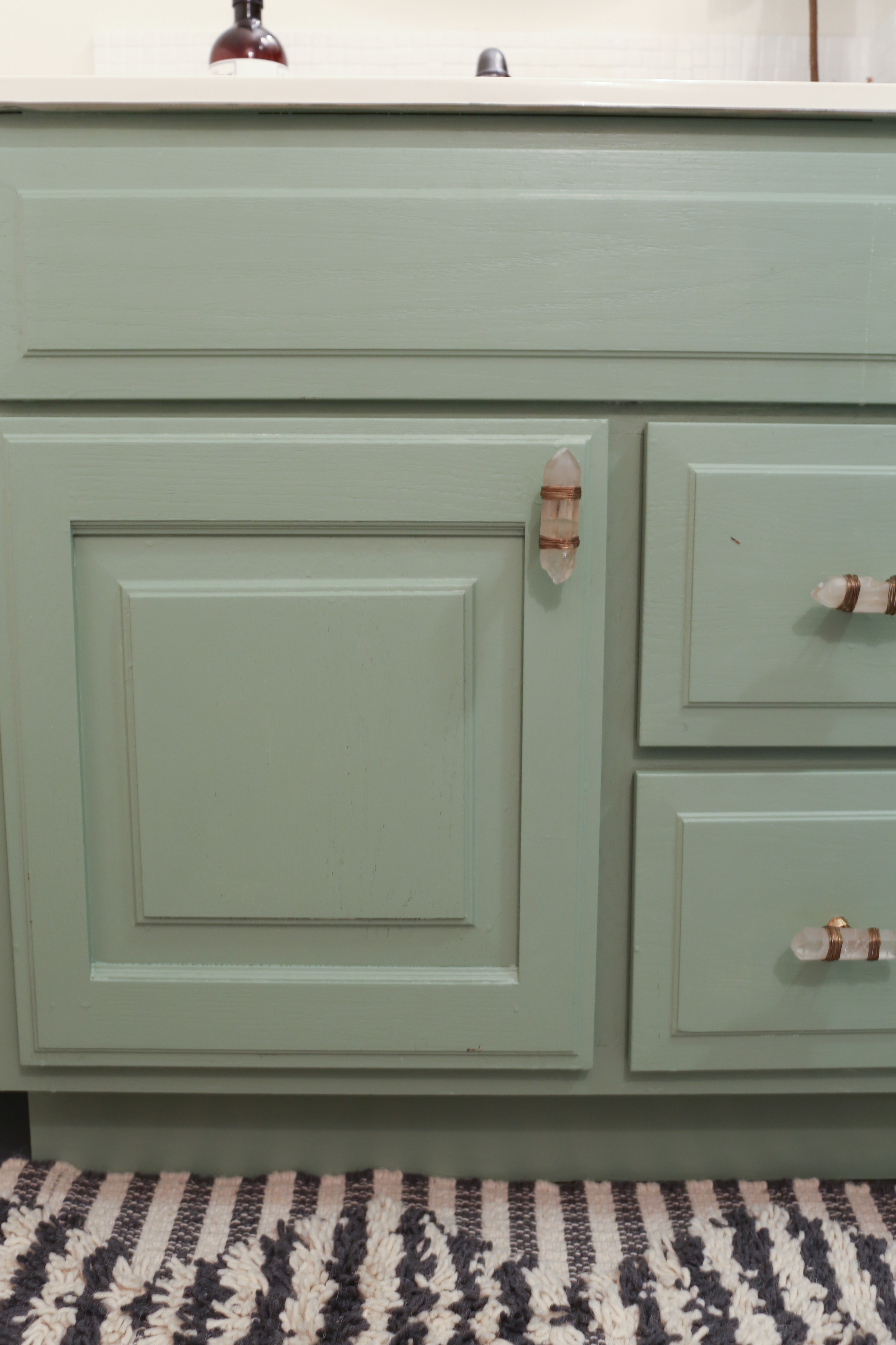 The bathroom cabinet is repainted green and basic knobs are updated with quarts cabinet pulls.