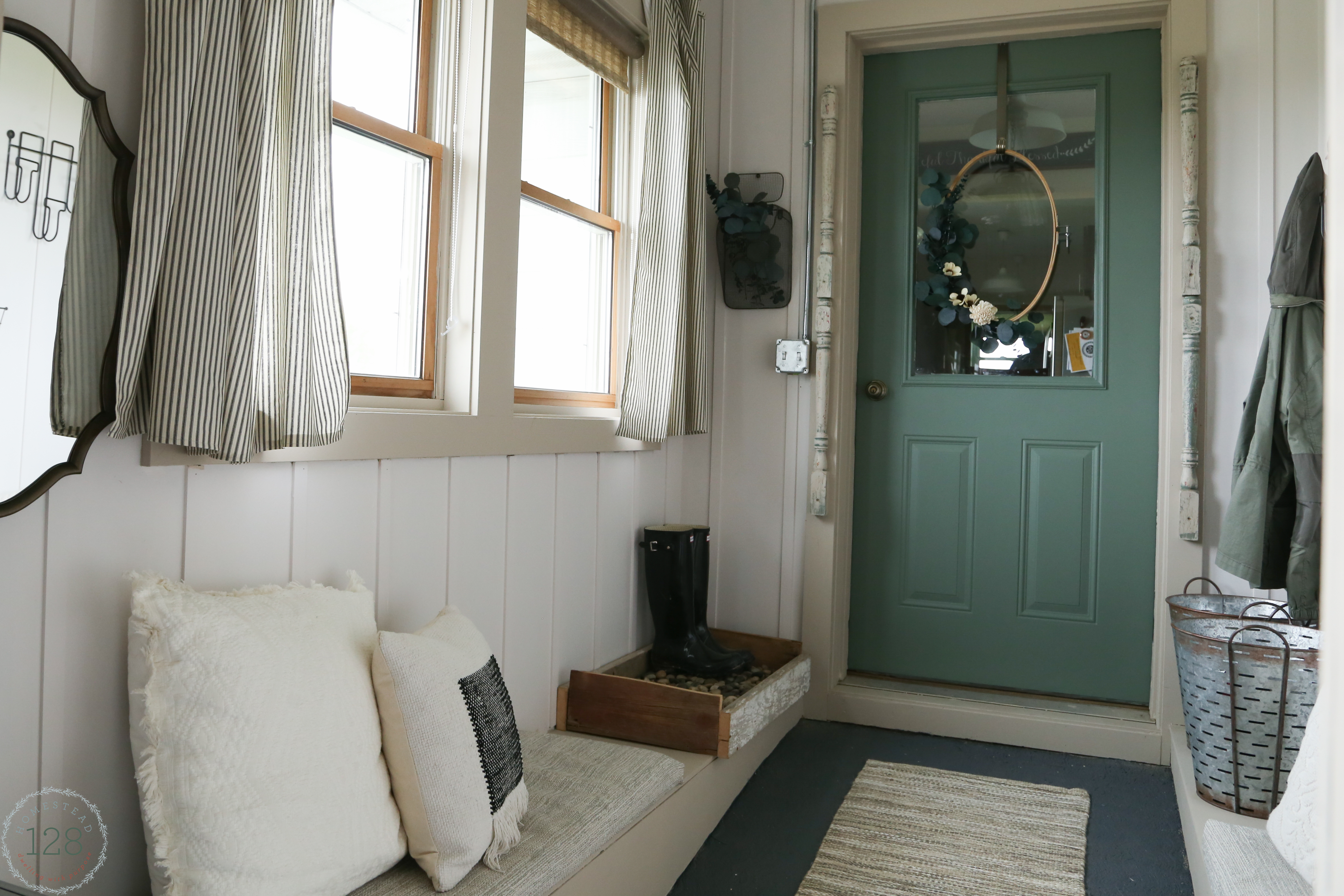 Farmhouse mudroom green front door with eucalyptus hoop wreath.