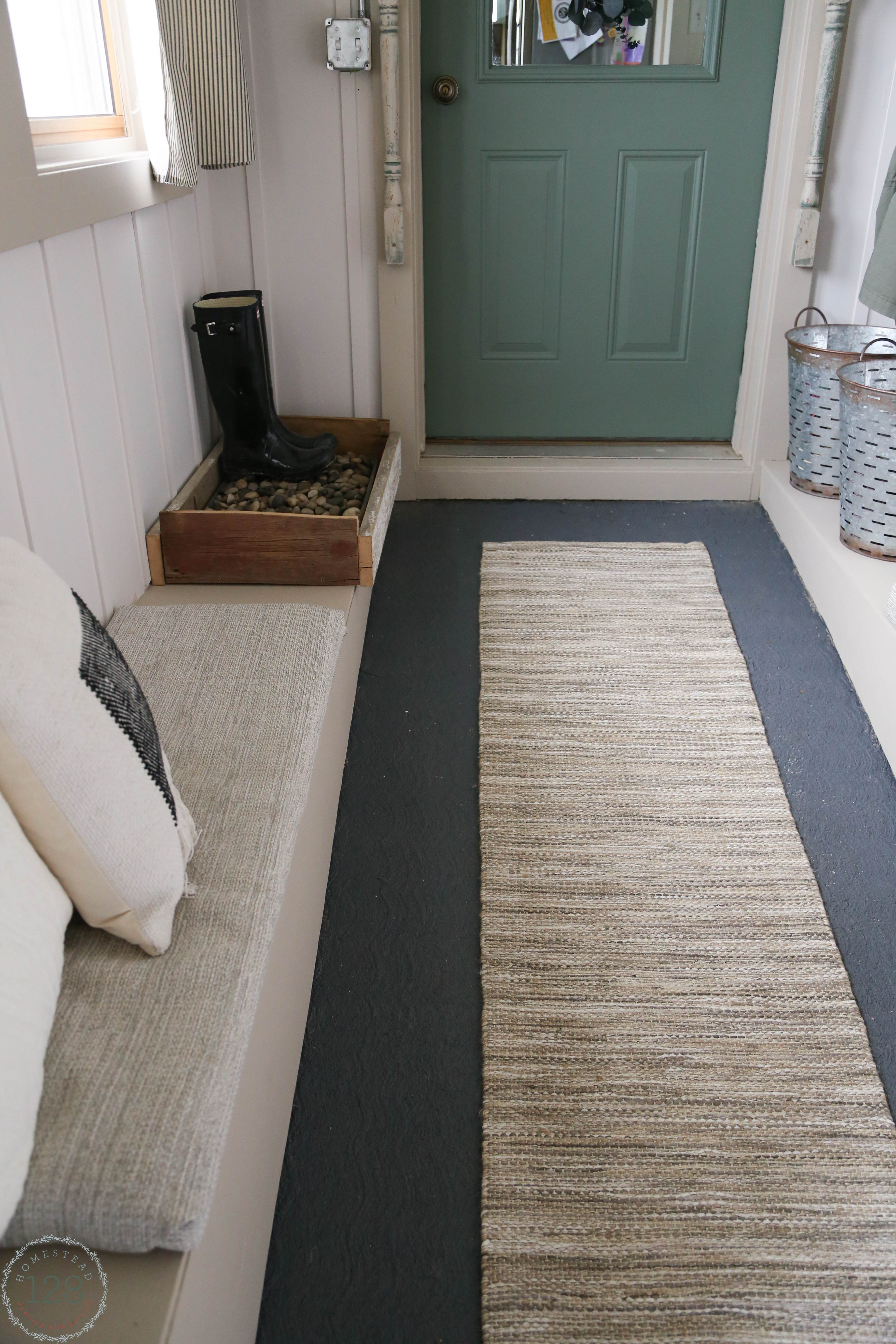 Gray painted cement flooring, upholstered benches, and shoe storage in the farmhouse mudroom with batten walls.