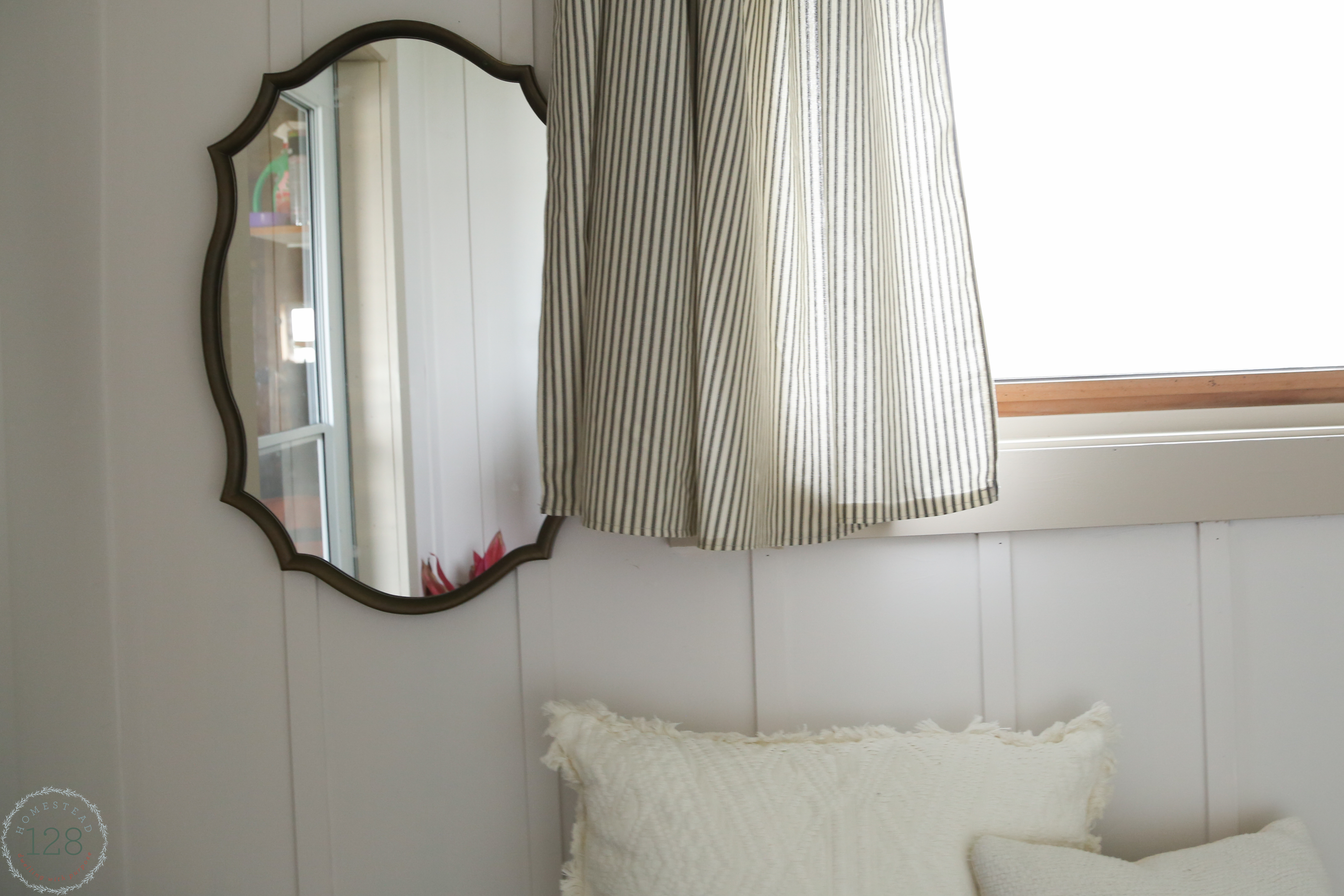 Vintage inspired gold trimmed mirror with black ticking striped curtains, greige trim and white batten walls.