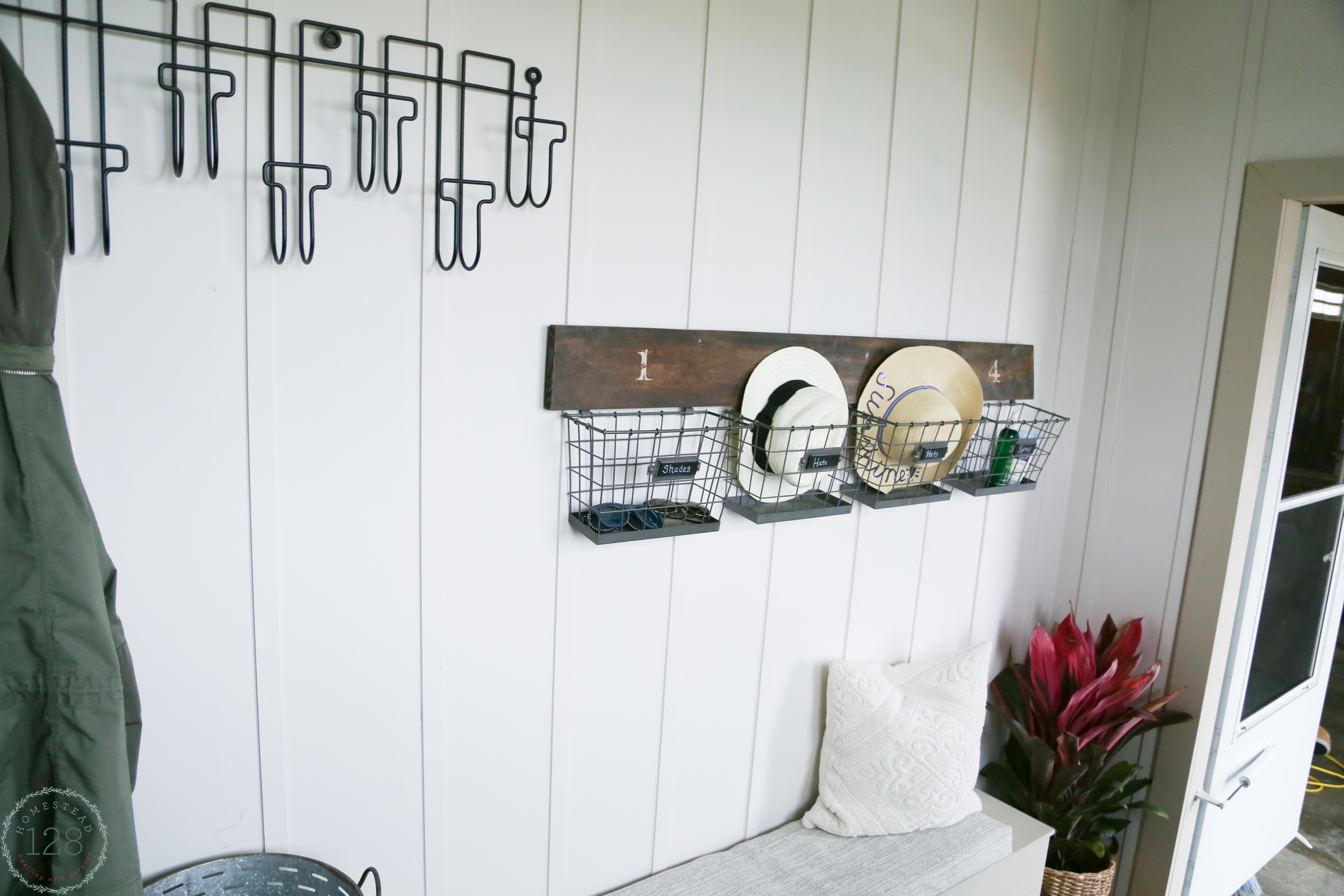 Farmhouse mudroom with white batten walls, black metal hooks and upholstered seats.