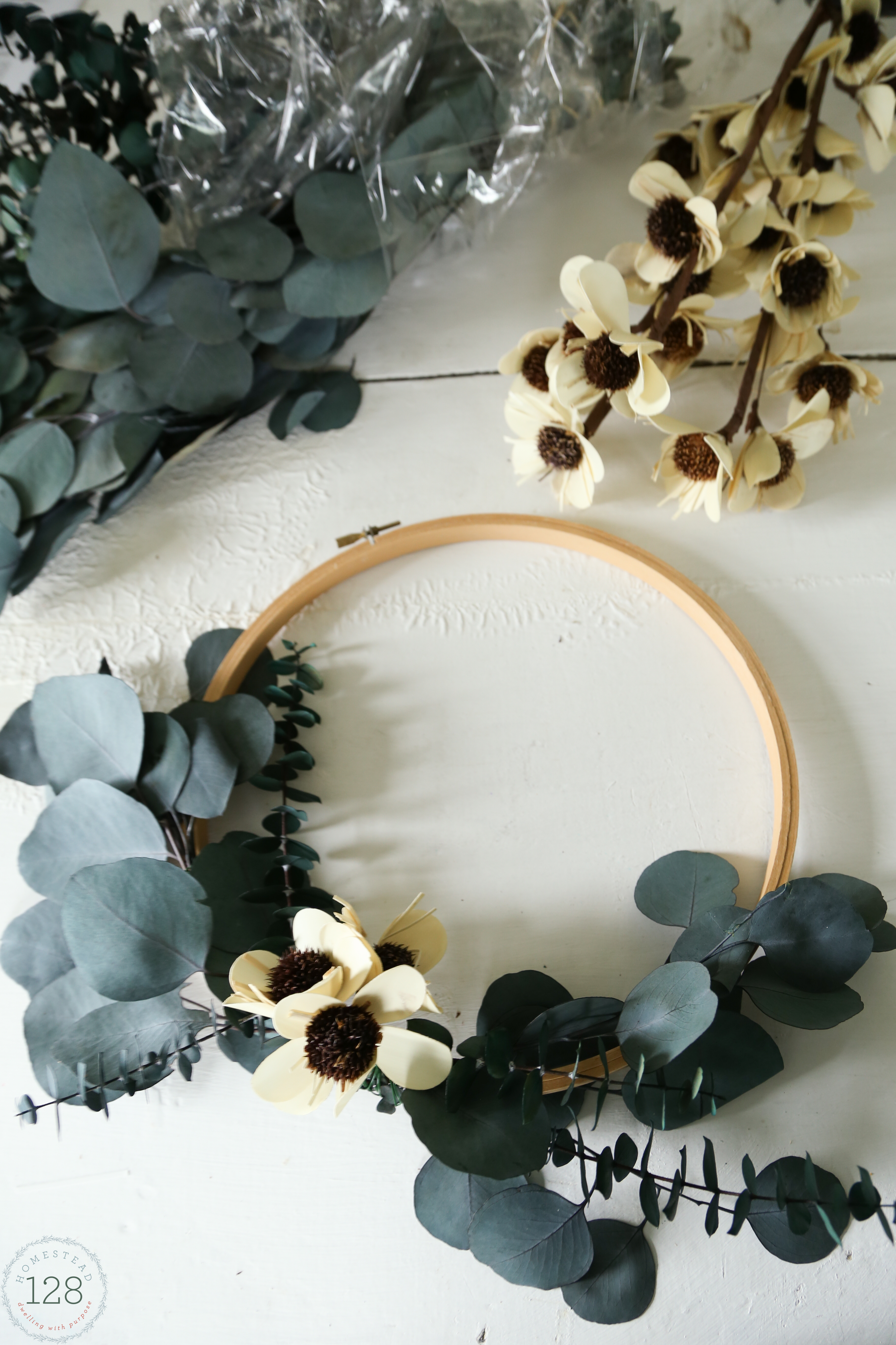 Eucalyptus and white flowered wreath made from embroidery hoops. An easy eucalyptus wreath DIY.