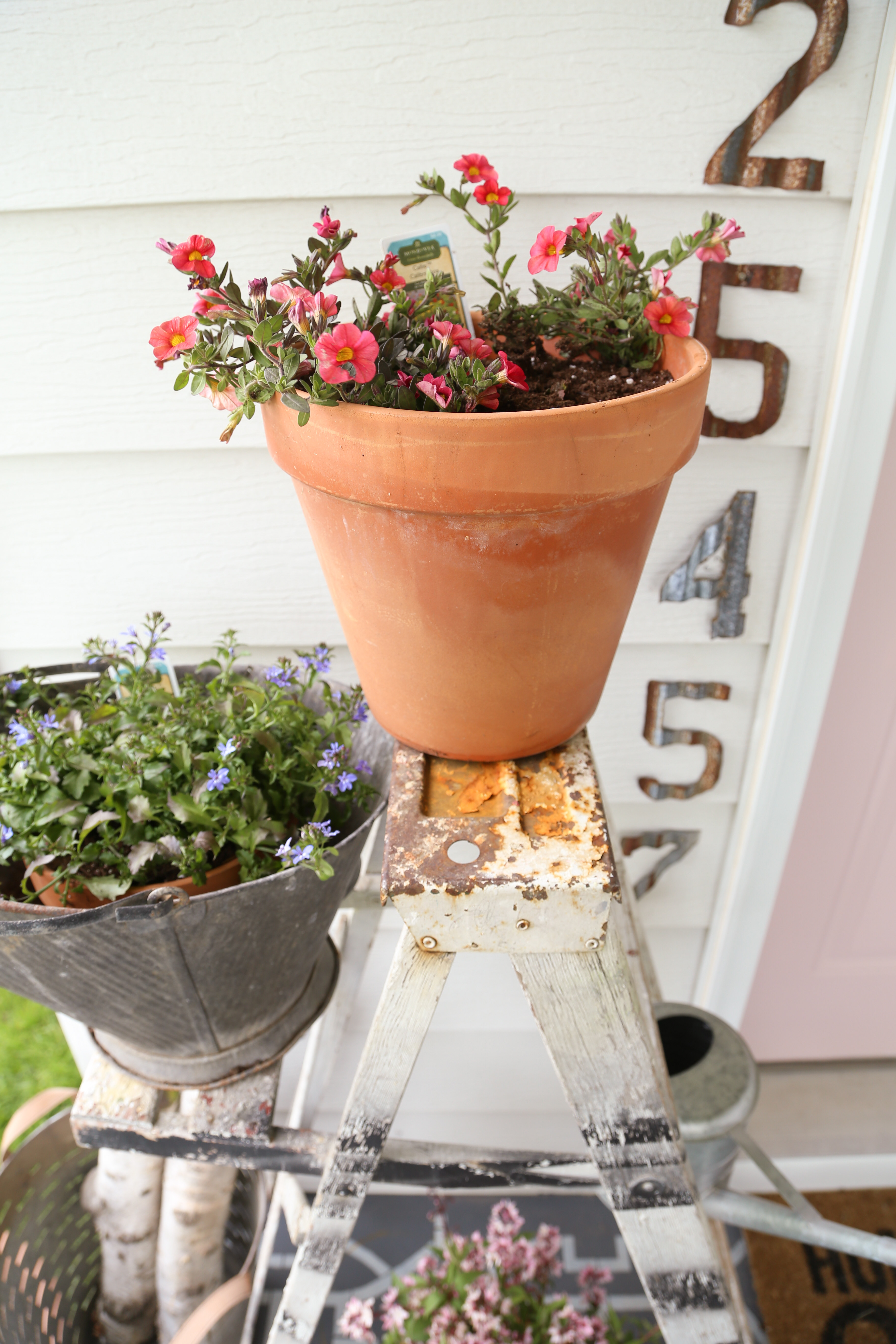Rusty ladder and galvanized bucket bring interest to a colorful farmhouse front porch.