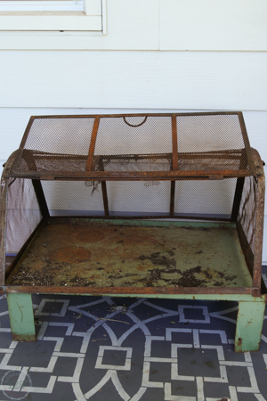 A vintage and rusty green metal greenhouse is used on the farmhouse front porch.  From Homestead 128.