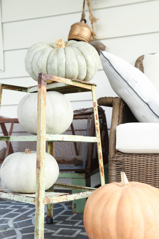 The farmhouse fall front porch is decorated with rusty green metal and muted green and orange pumpkins.