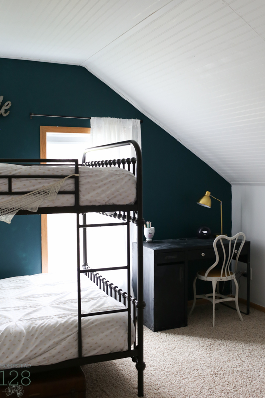 Dark green walls and beadboard ceilings in the shared girl bedroom.