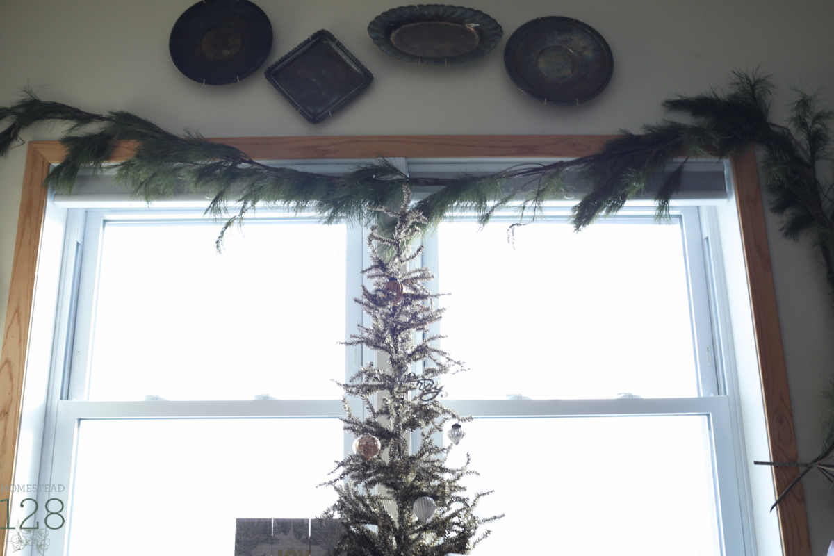 Golden tinsel tree and garland in the kitchen window at the Christmas farmhouse.