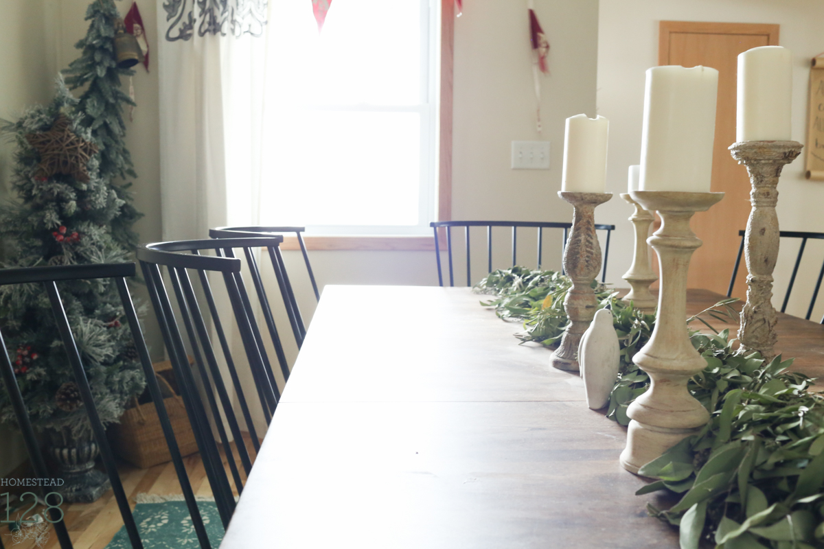 Clean and modern farmhouse Christmas table is draped with a eucalyptus and olive leaf garland and large white candles.