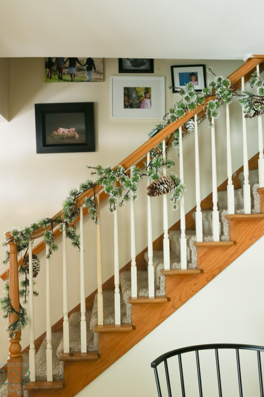 Flocked pine garland and pinecones cover the farmhouse steps.