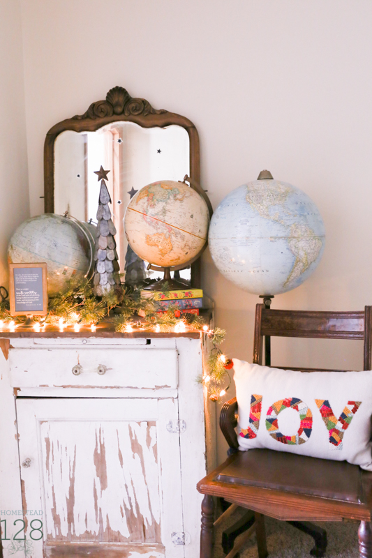 Farmhouse Christmas decorating. Chippy white cupboard is decorated with an assortment of globes, a tin Christmas tree and colorful pillow.