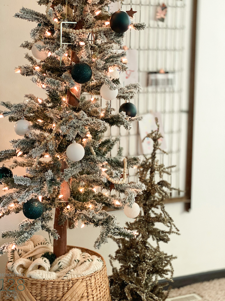 A flocked alpine style Christmas tree decorated with whites and sea green.